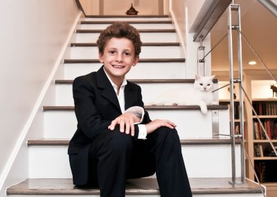 Boy in a suit seated on stairs with his white cat, both looking straight into the camera.