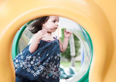 Girl in playground with dress and hair blowing in the wind.