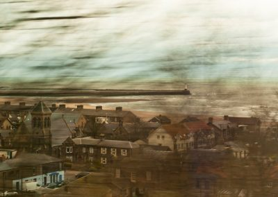 Blurry image of a seaside village in the United Kingdom taken from a train.