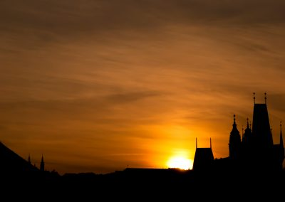 Orange sunset behind the spires seen from the Charles Bridge into Malá Strana in Prague, Czech Republic.