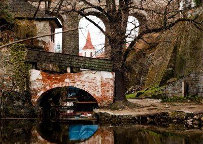 View by the river and through a bridge in Český Krumlov, Czech Republic.