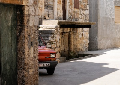 An old, red car peeks out from a building made of stone in Croatia.
