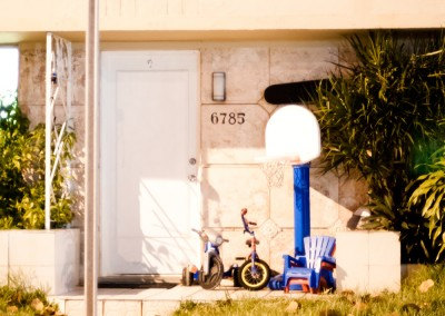 Children's basketball net, tricycles, and chairs outside a small apartment in Miami.