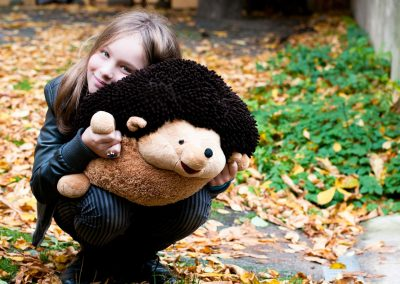 Young girl hugs a giant stuffed hedgehog on an autumnal rooftop.